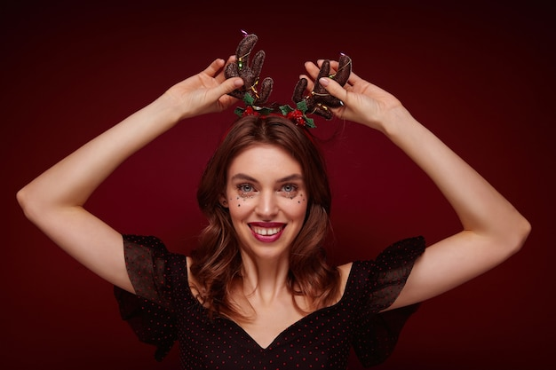 Charming young brown haired female in festive clothes raising hands to head horns and smiling widely, enjoying x-mas theme party, isolated