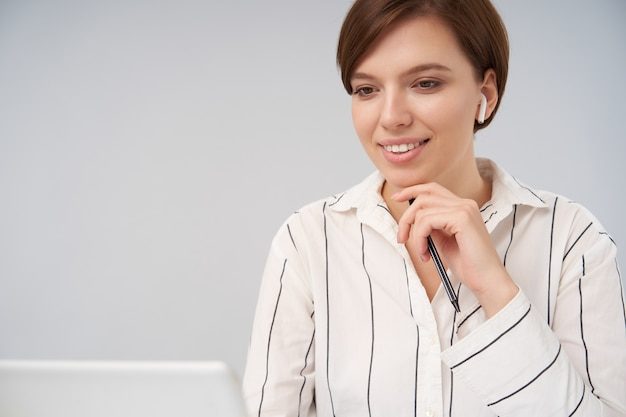 自然なメイクで魅力的な若い茶色の髪の女性は、上げられた手で彼女のあごに優しく触れ、白で隔離された心地よい笑顔で先を見据えています