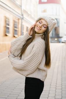 산책에 매력적인 젊은 갈색 머리 여자. 니트 따뜻한 모자에 세련된 이미지의 아름답고 행복한 여자. 도시 산책, 라이프 스타일