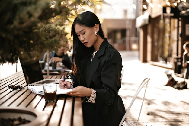 Charming young brunette lady in black trench coat make notes in notebook and works in laptop