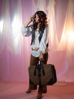 70年代のスタイル、ヒッピースタイルの服を着た長い巻き毛の魅力的な若いブルネット。若い女性がスーツケースを持って全国を旅しています