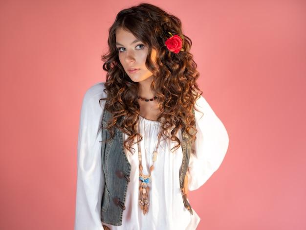 のスタイルの服で長い巻き毛を持つ魅力的な若いブルネット