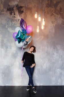 Charming young brunette woman holding a large bundle of helium balloons