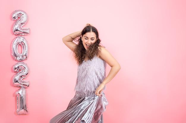 Очаровательная молодая брюнетка с вьющимися волосами в серебряном праздничном наряде танцует на розовой стене с серебряными воздушными шарами для новогодней концепции