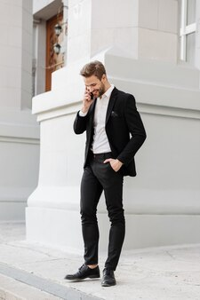 Очаровательный молодой бизнесмен в костюме, стоящий в городе, с помощью мобильного телефона