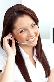 Charming young businesswoman wearing headphones smiling at the camera