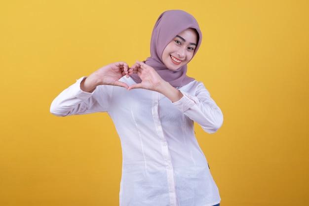 자연스러운 메이크업으로 매력적인 젊은 쾌활한 아시아 여성, 제기 손으로 마음을 형성하고 노란색 벽 위에 서서 정면에 넓게 웃고