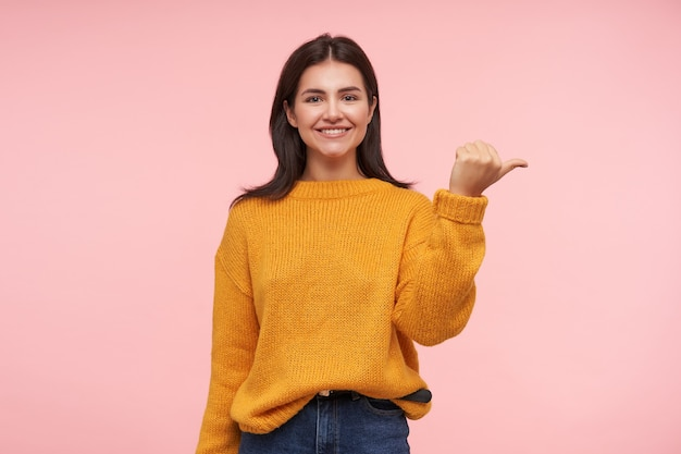 Charming young cheerful brown haired woman with loose hair keeping her hands raised while showing aside and smiling pleasantly, standing over pink wall