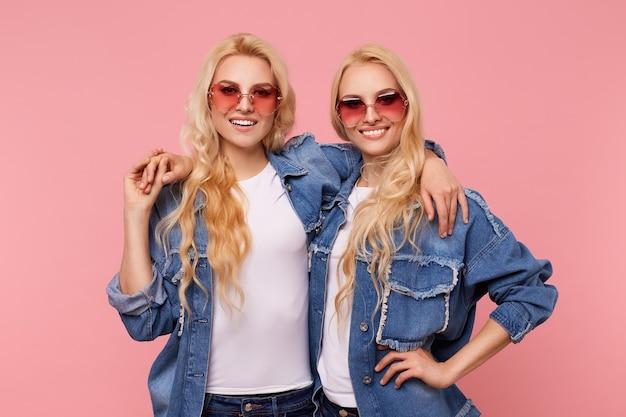 분홍색 배경 위에 서서 서로 사랑스럽게 포옹하고 카메라를 행복하게보고있는 빨간 선글라스에 매력적인 젊은 쾌활한 장발 흰머리 자매