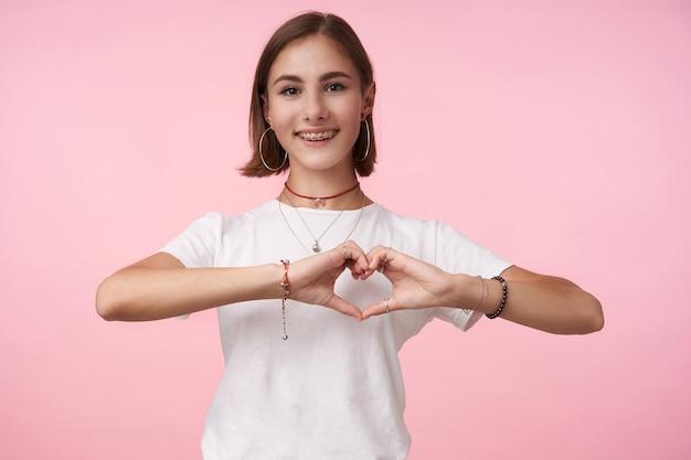 Affascinante giovane donna bruna dai capelli corti allegra con trucco naturale che forma il cuore con le mani alzate e sorridente ampiamente davanti, in piedi sul muro rosa