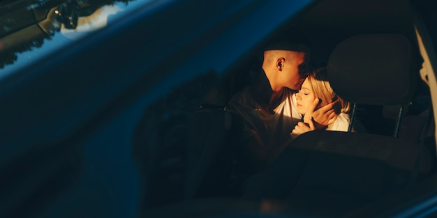 Charming young couple embracing and kissing in the car while traveling in their vacation time.