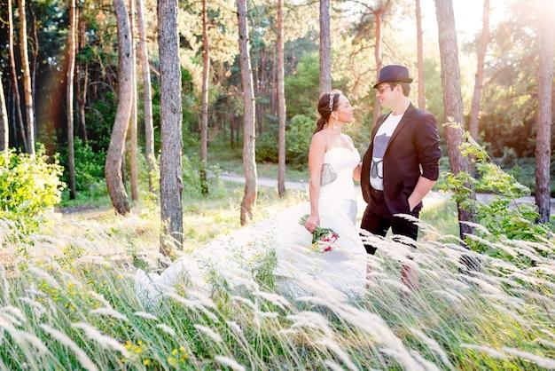 魅力的な若いカップルは、背の高い草のある畑でポーズをとっている白いドレスと新郎のスーツと帽子の美しい女性と結婚しました。
