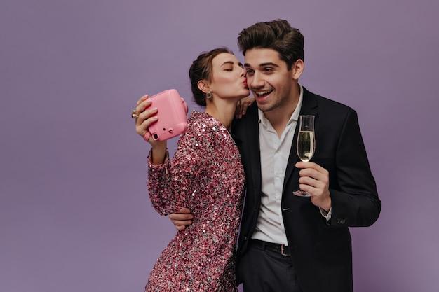 Affascinante giovane coppia in abiti da festa che si diverte con la macchina fotografica, fa foto, beve vino e posa adorabile contro il muro viola chiaro