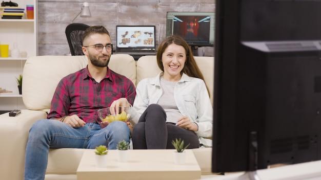 ソファに座って、チップを楽しみながらテレビを見ている魅力的な若いカップル。