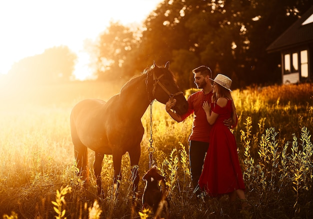Charming young couple stands with a brown horse before a country house