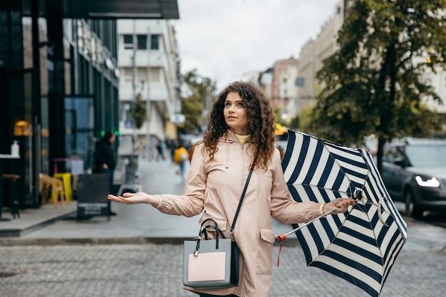 Очаровательная молодая кудрявая женщина-метис под зонтиком гуляет по улице мегаполиса в дождливый день