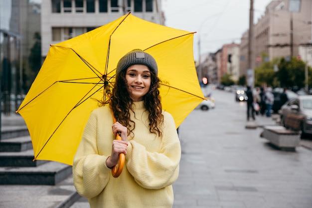 Очаровательная молодая кудрявая женщина использует желтый зонтик на улице мегаполиса в дождливый день