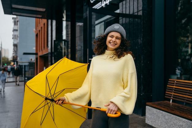 Очаровательная молодая кудрявая женщина идет по улице