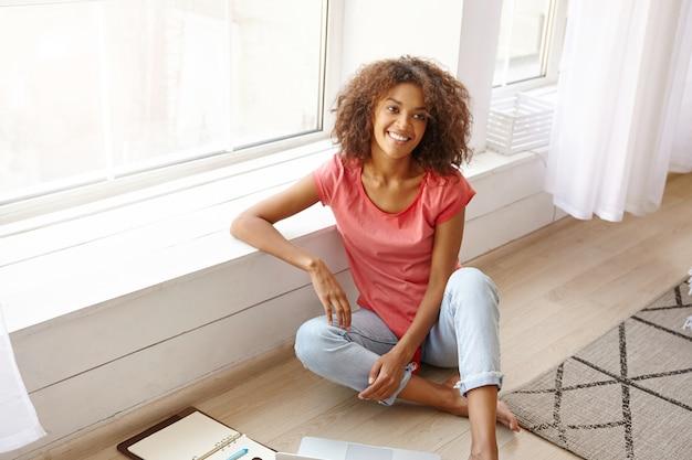 Affascinante giovane donna riccia con la pelle scura seduto vicino alla finestra in una luminosa giornata di sole, sorridente ampiamente ed essere di buon umore, indossando abiti casual