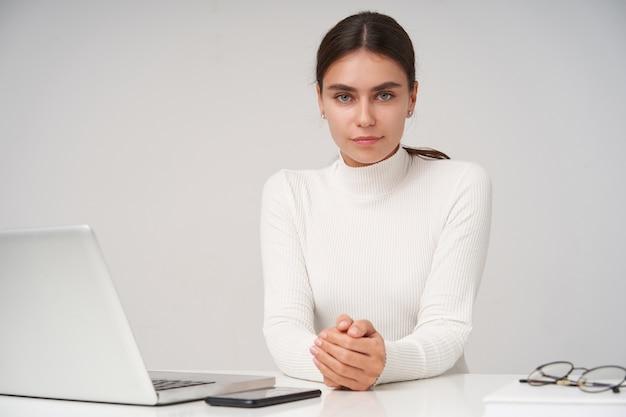 Affascinante giovane signora dagli occhi azzurri dai capelli scuri con trucco naturale guardando con viso calmo e tenendo le mani sul tavolo mentre posa sopra il muro bianco