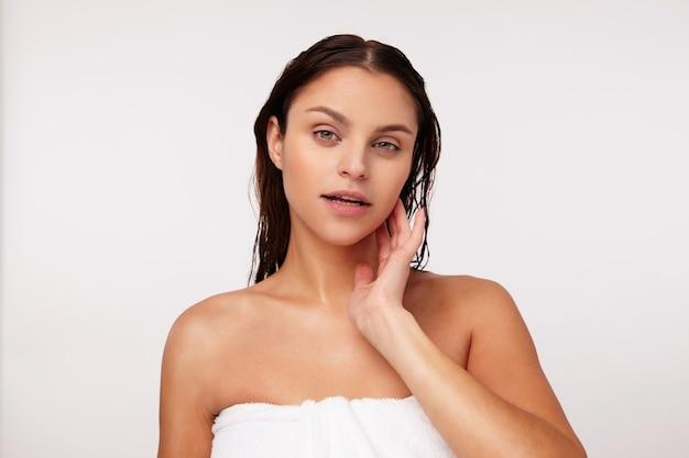 Affascinante giovane signora dagli occhi verdi dai capelli scuri senza trucco toccando morbidamente la sua guancia e guardando con calma, in posa dopo la doccia