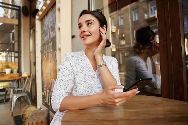 흰색 폴카 도트 옷을 입은 매력적인 젊은 검은 머리 아가씨는 손을 들고 부드럽게 얼굴을 만지고 꿈꾸는듯한 옆으로보고 카페 인테리어 위에 테이블에 포즈를 취합니다.