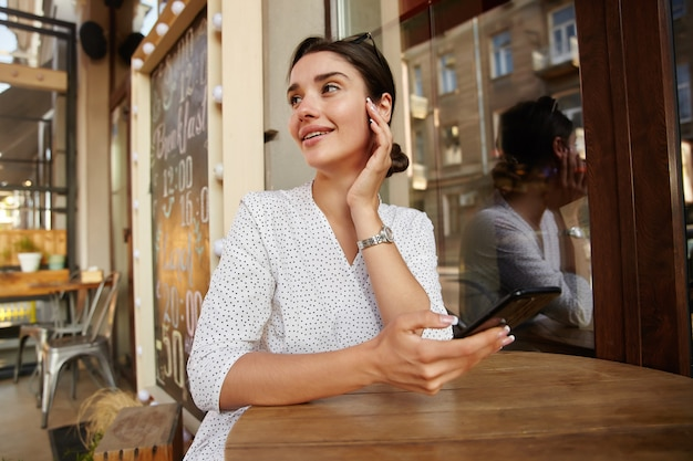 Charming young dark haired lady in white polka-dot clothes touching her face gently with raised hand and looking dreamily aside, posing at table over cafe interior