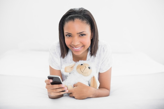 Charming young dark haired model holding a mobile phone and a plush sheep