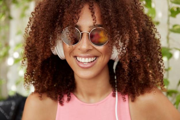 魅力的な若い黒肌のアフリカ系アメリカ人の女性音楽愛好家は、カフェテリアでお気に入りの曲を楽しんだり、ヘッドフォンでプレイリストから素晴らしい作曲を聴いたりしています。人、ライフスタイル、休息のコンセプト