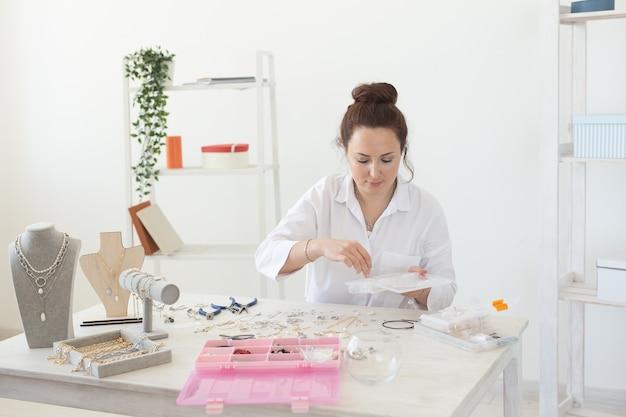 매력적인 젊은 백인 여성이 책상에 앉아 아름다운 독특한 의상 보석을 만들고 있습니다. 취미와 즐거운 일의 개념