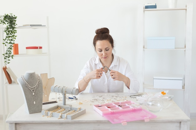 앉아있는 동안 아름다운 독특한 의상 보석을 만드는 매력적인 젊은 열정적 인 백인 여성