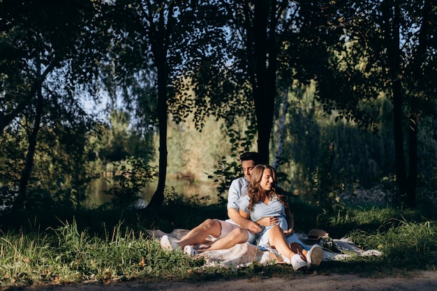 Charming young expecting couple rest on the plaid under green tree