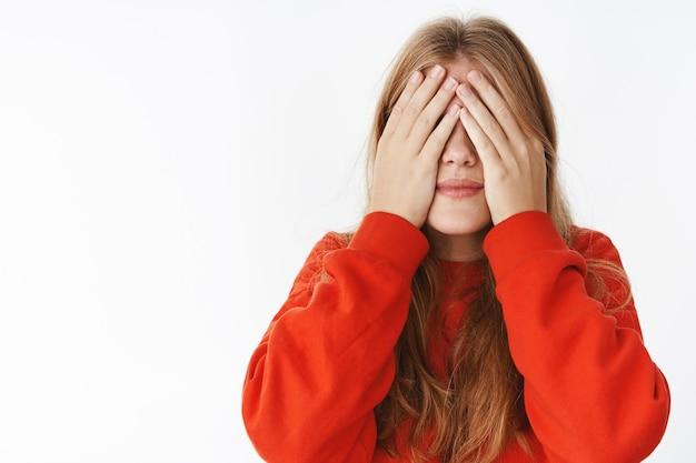 赤いスタイリッシュな暖かいセーターの魅力的な若い金髪の女性は、10を数えて顔に手のひらで目を閉じ、期待と喜びで驚きを待って、灰色の壁の上に穏やかで夢のようなポーズをとる