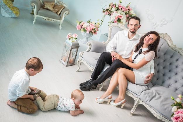 魅力的な若い家族愛する夫と妻が美しいリビングルームの床で遊んでいる2人のかわいい息子の隣のソファに座っています