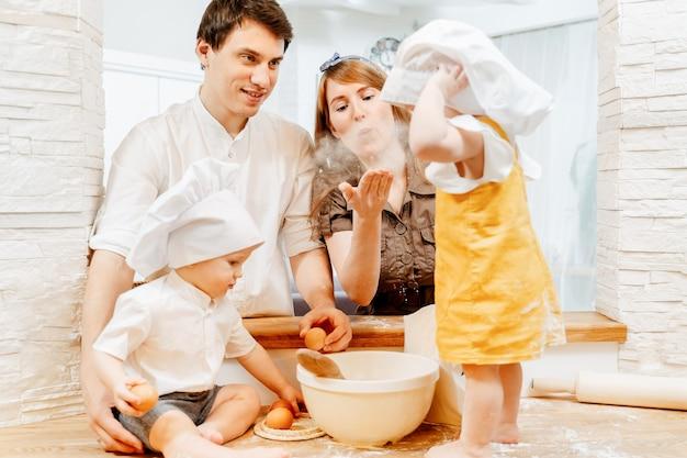 魅力的な若い家族のお父さんのお母さんと料理の服を着た2歳の兄と妹が、居心地の良いキッチンでパイの生地を準備しています。週末の家族の家を一緒にコンセプト