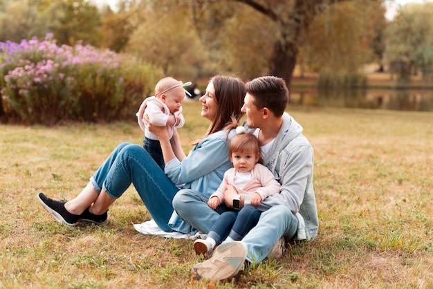 일몰 동안 공원에서 작은 아이들과 함께 야외 재미 매력적인 젊은 가족