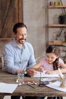 魅力的な若い父親と彼の小柄で楽しい娘がテーブルに座って水彩絵の具で絵を描いて、一緒にそれを喜んでやっています
