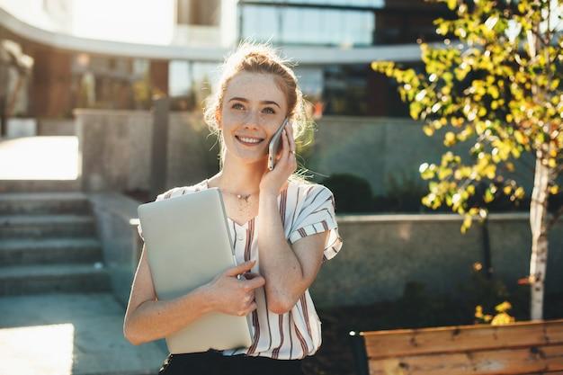 매력적인 젊은 여성 프리랜서가 새로운 건물에 대해 lapott를 들고 웃고 전화로 이야기