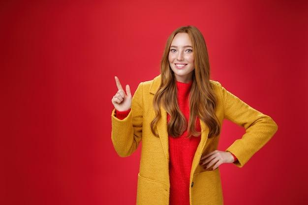 노란색 코트를 입은 매력적인 젊은 여성이 허리에 손을 잡고 왼쪽 상단을 가리키며 좋은 분위기에서 빨간색 배경 위에 흥미로운 제안을 보여주거나 홍보하면서 활짝 웃고 있습니다.