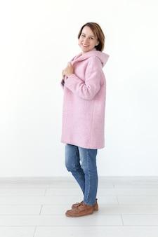 디자이너 핑크 코트에 흰색 배경에 포즈 매력적인 젊은 여성 모델. 독특한 수공예 디자인의 개념. 광고 공간, copyspace