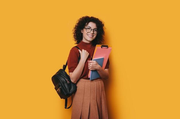 노란색 벽에 그녀의 공부 책을 잡고 웃 고 카메라를보고 안경을 쓰고 곱슬 머리를 가진 매력적인 젊은 여성 학생.
