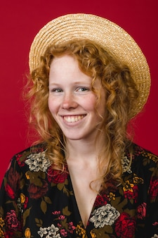 Charming young ginger woman smiling and looking at camera