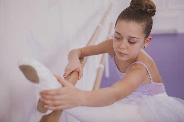 Charming young girl ballerina exercising at dance school