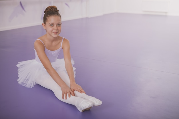 Charming young girl ballerina exercising at dance school