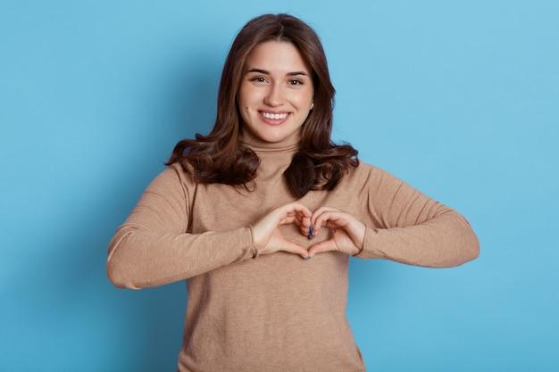 Очаровательная молодая девушка признается в любви, показывает жест сердца пальцами, широко улыбается