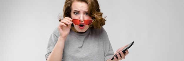 Charming young girl in a gray t-shirt on a gray background. girl in red glasses with phone
