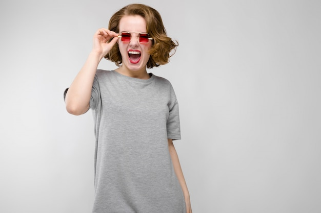 Charming young girl in a gray t-shirt on a gray background. girl in red square-eyed glasses.