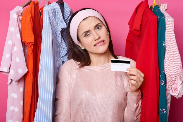 Charming young girl has bank card in hand. attractive lady spends all money for buying clothes. female wants to buy expensive dress. woman stands curving lips near shirts. colorful blouses on hangers.