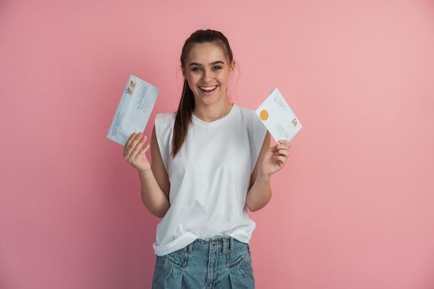Очаровательная молодая девушка держит конверты с почтовыми марками