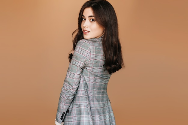 灰色のジャケットの魅力的な若い女の子。屋内でフレンドリーな黒髪の女性のスナップショット。